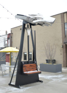 A picture of a sculpture called Keeping Time located in TIme Piece Park, Charlotte Michigan shows a metal hand playing a keyboard sitting on top of a bench that moves the keyboard when sitting.